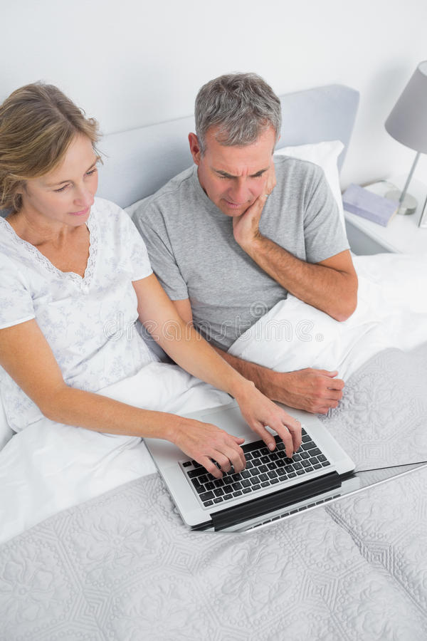 Download Thoughtful Couple Using Their Laptop Together In Bed Stock Image - Image: 33051353