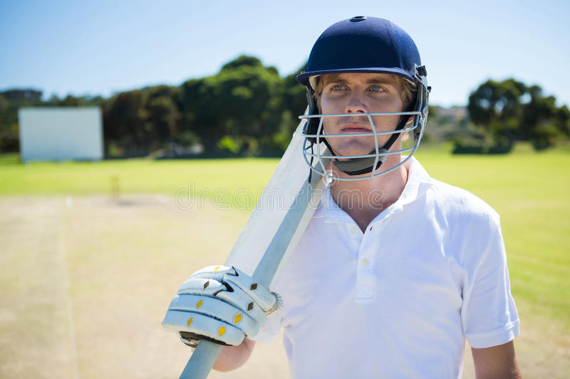 Thoughtful cricket player holding bat while wearing helmet. At field on sunny day royalty free stock photography
