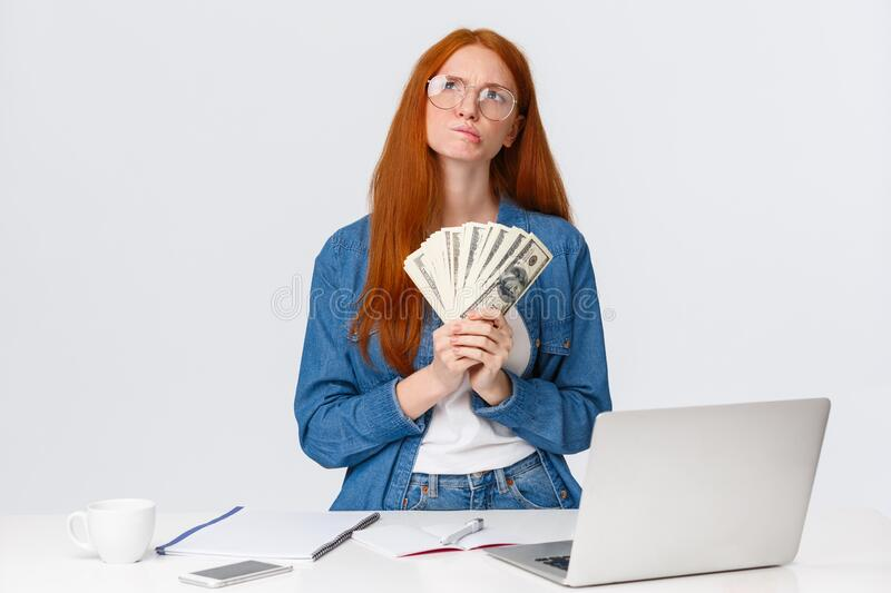 Thoughtful and curious good-looking redhead girl winning prize internet competition, artwork challenge online, holding royalty free stock images
