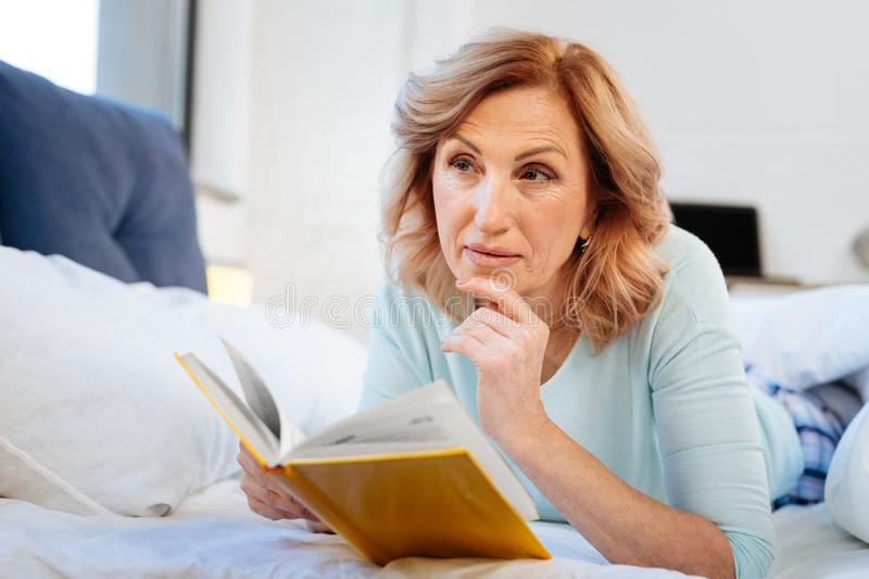 Thoughtful curious mature woman wearing comfortable domestic clothes royalty free stock photos