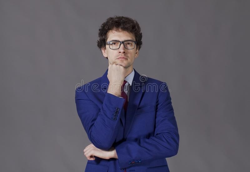 Thoughtful curly boy standing with blue jacket and glasses stock image