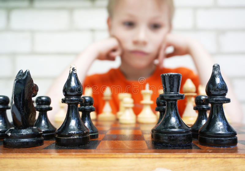 Thoughtful cute boy playing checkmate. Little boy sits at the table with a board of checkmate stock images