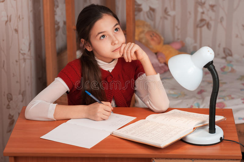 Thoughtful girl doing homework at the table stock image