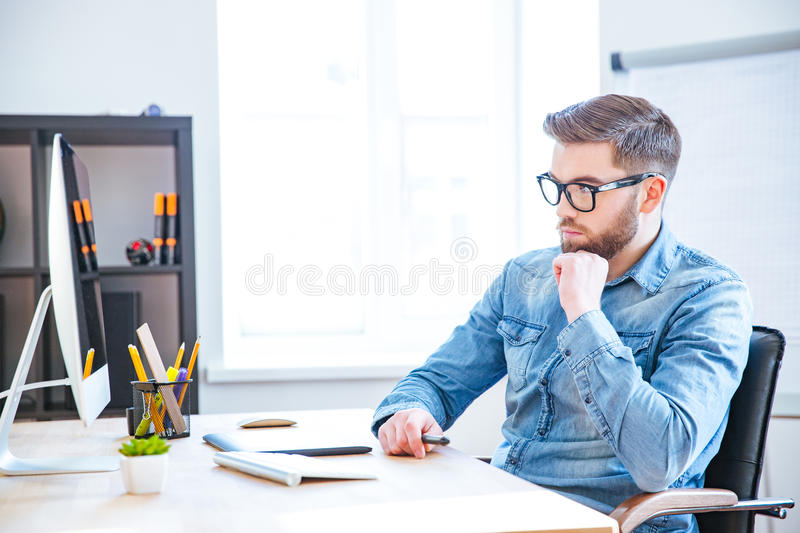 Thoughtful designer using graphic tablet and computer stock photo