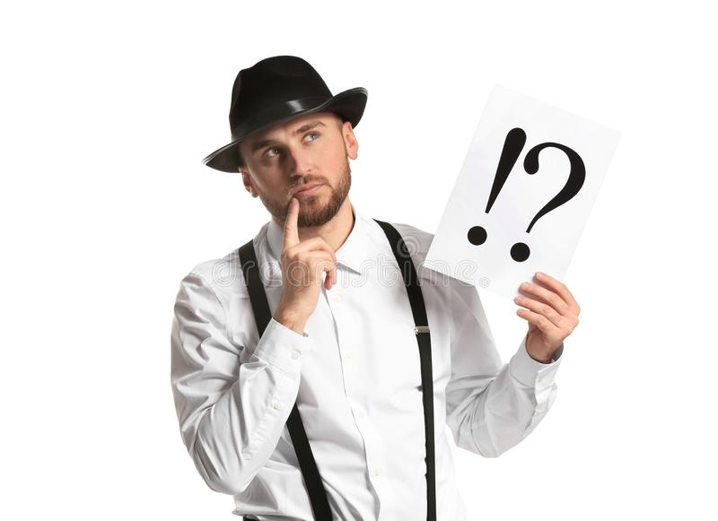 Thoughtful detective holding sheet of paper with exclamation and interrogation marks on white background royalty free stock photos