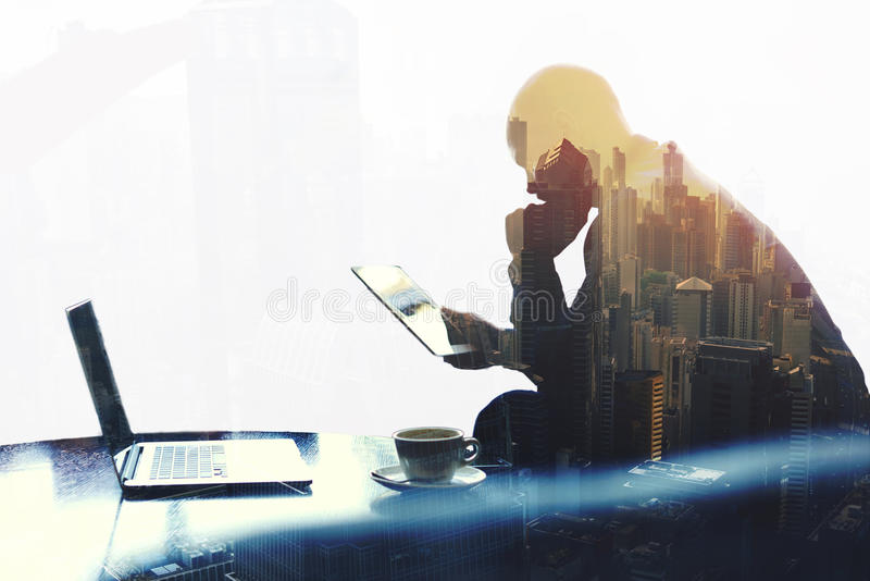 Thoughtful economist is reading news in network via digital tablet. Double exposure silhouette of man skilled managing director is analyzing activities of the stock image