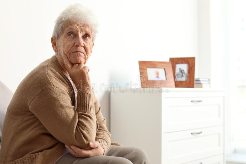Thoughtful elderly woman at home. Space for stock photo