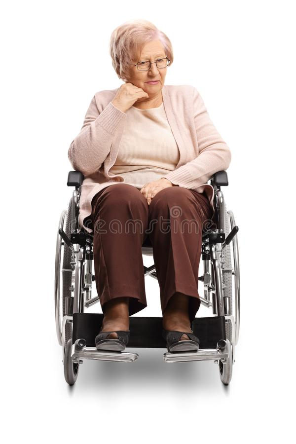 Thoughtful elderly woman sitting in a wheelchair. Isolated on white background stock photography
