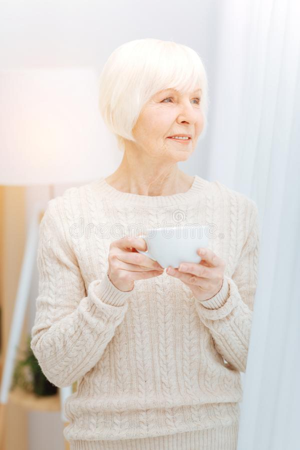 Thoughtful elderly woman standing near the window and holding a cup stock image
