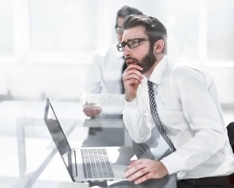 Thoughtful employee sitting at the office Desk. Business concept royalty free stock image
