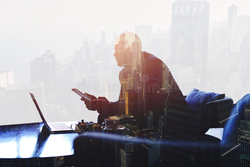 Thoughtful entrepreneur is using digital tablet and laptop computer for finance analyze. Double exposure silhouette of successful businessman is working in stock photo