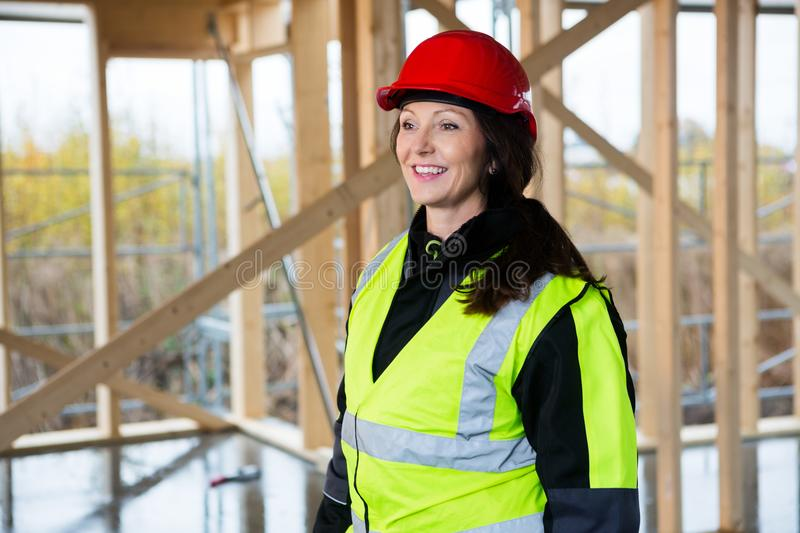 Thoughtful Female Carpenter In Protective Wear At Site. Thoughtful female carpenter in protective wear looking away at construction site stock images