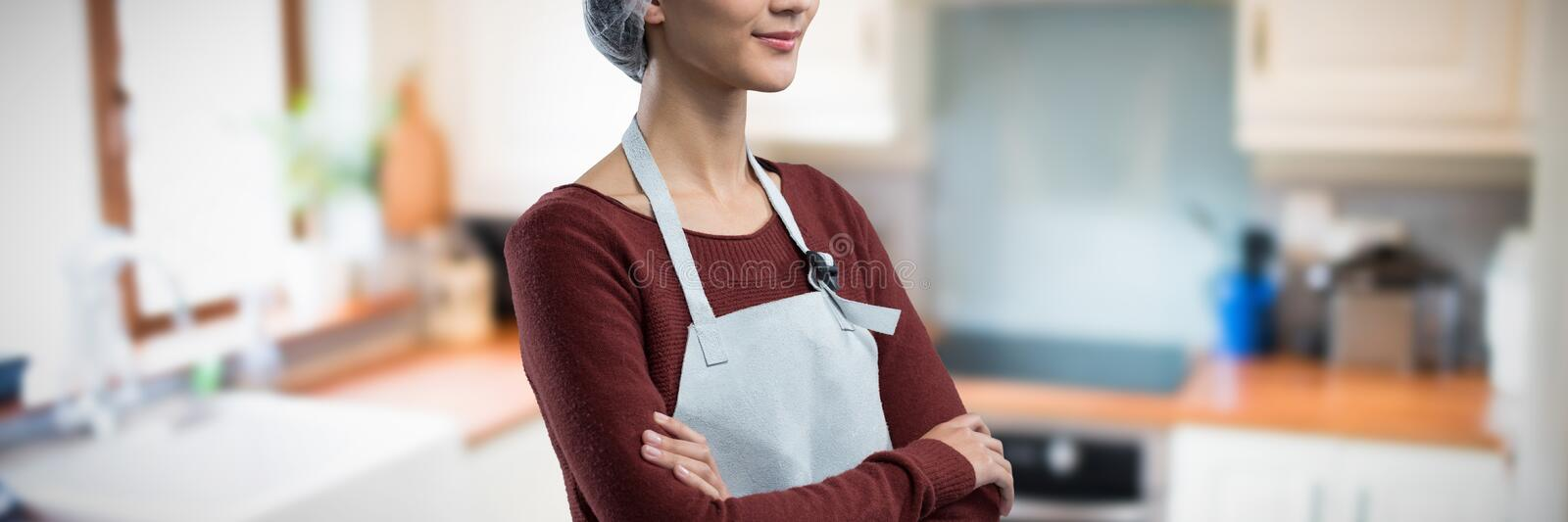 Composite image of thoughtful female chef standing with arms crossed. Thoughtful female chef standing with arms crossed against view of a kitchen stock photos