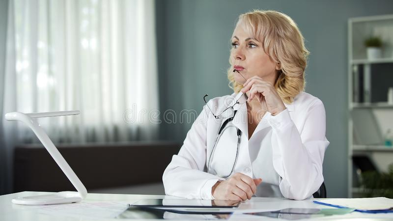 Thoughtful female doctor sitting at table, analysing patient results, diagnosis. Stock photo royalty free stock photo