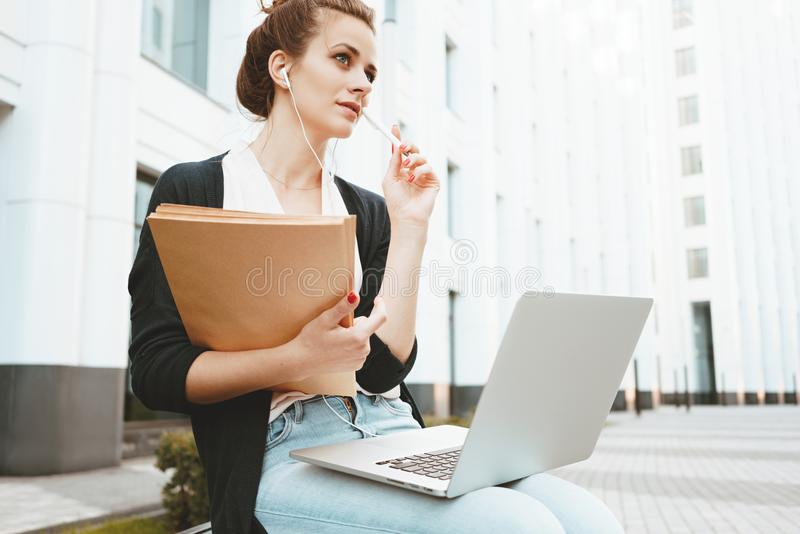 Young teacher prepares for lecture and searches for information on Internet with a laptop computer sitting on urban street. Thoughtful female student sits in royalty free stock photos