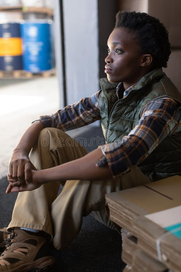 Thoughtful female worker sitting in warehouse. Close-up of thoughtful African-american female worker sitting in warehouse. This is a freight transportation and royalty free stock images