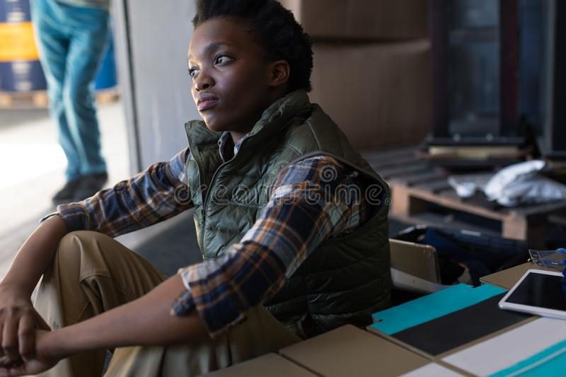 Thoughtful female worker sitting in warehouse. Side view of African-american thoughtful female worker sitting in warehouse. This is a freight transportation and stock photography