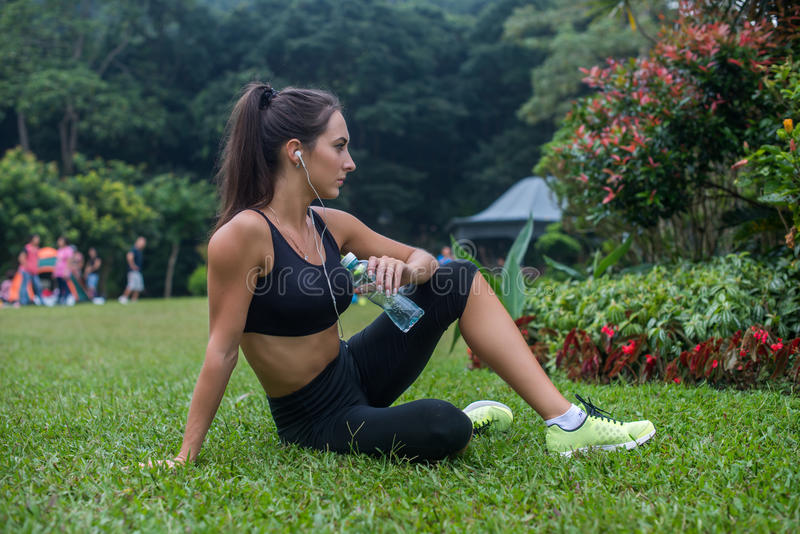 Thoughtful fitness girl sitting on grass in park resting after exercising or running, listening to music and holding a royalty free stock photo
