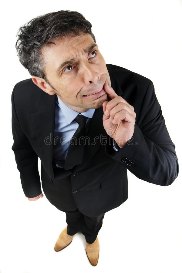 Thoughtful frowning businessman. High angle full length portrait of a thoughtful frowning businessman standing looking up with his finger to his mouth as he stock image