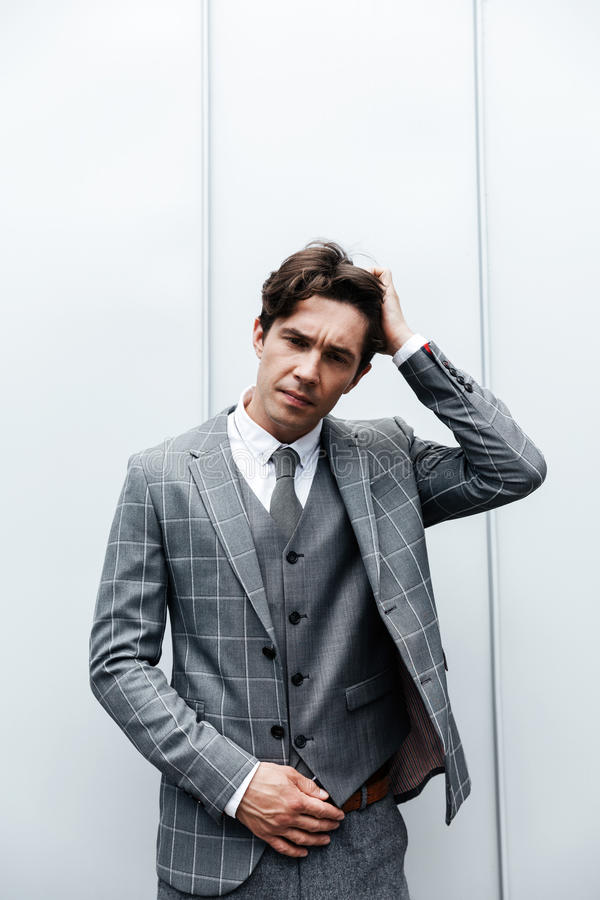 Thoughtful frowning man in suit standing royalty free stock photo