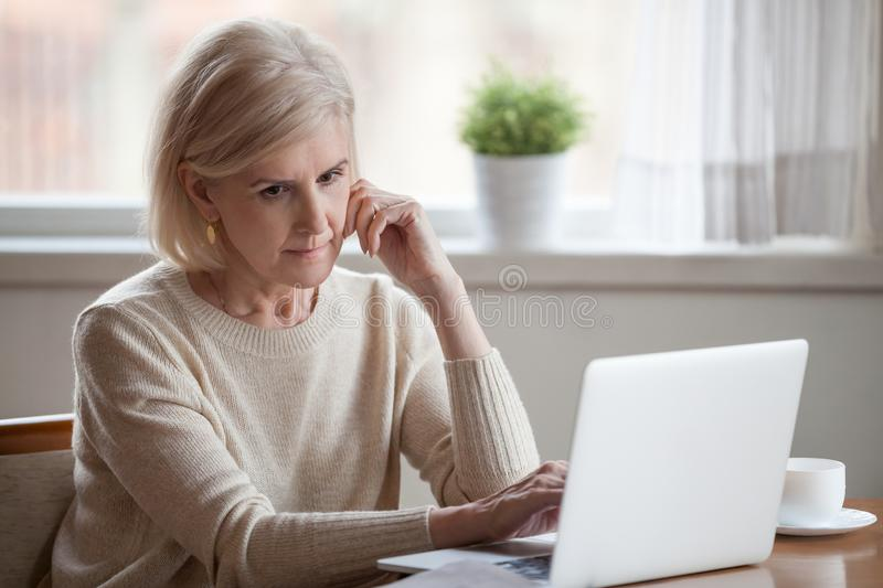 Thoughtful frustrated woman sitting at table near laptop. Frustrated grey hair sad middle aged woman sitting at table using computer. Distracted grandmother stock photo