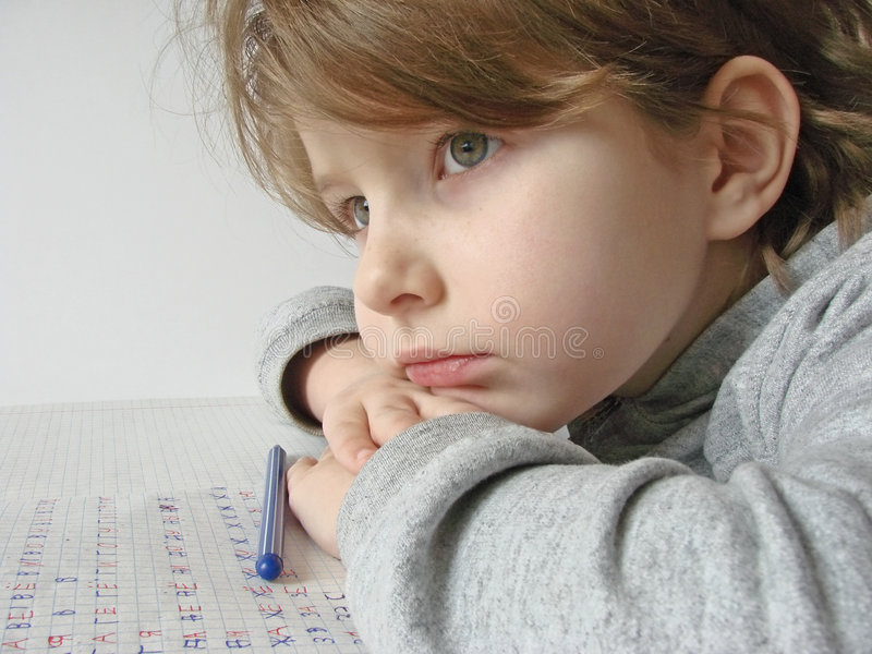 Thoughtful girl. Little thoughtful girl with pen and open workbook stock photo