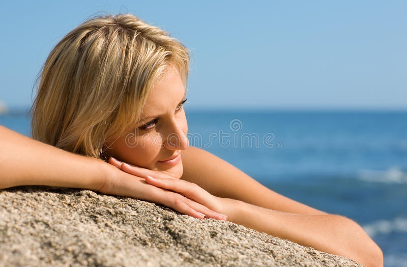 Thoughtful girl on the beach. By the sea royalty free stock image