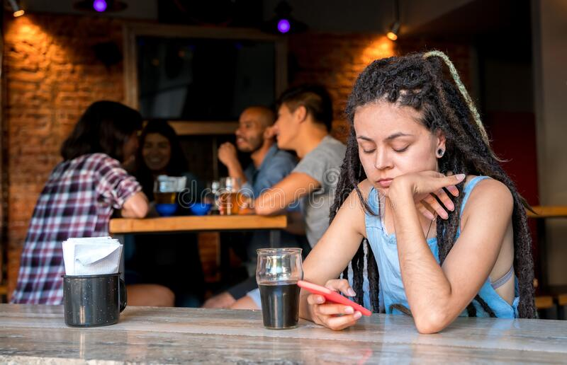 A girl alone with her phone in a bar stock photography