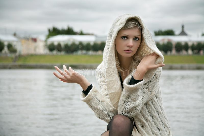 The thoughtful girl in knitted dress o. N a background of water royalty free stock photography
