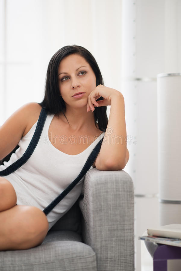 Thoughtful girl sitting on sofa in living room stock photography