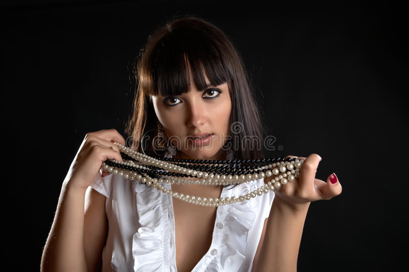 The thoughtful girl with pearl beads in hand stock photography
