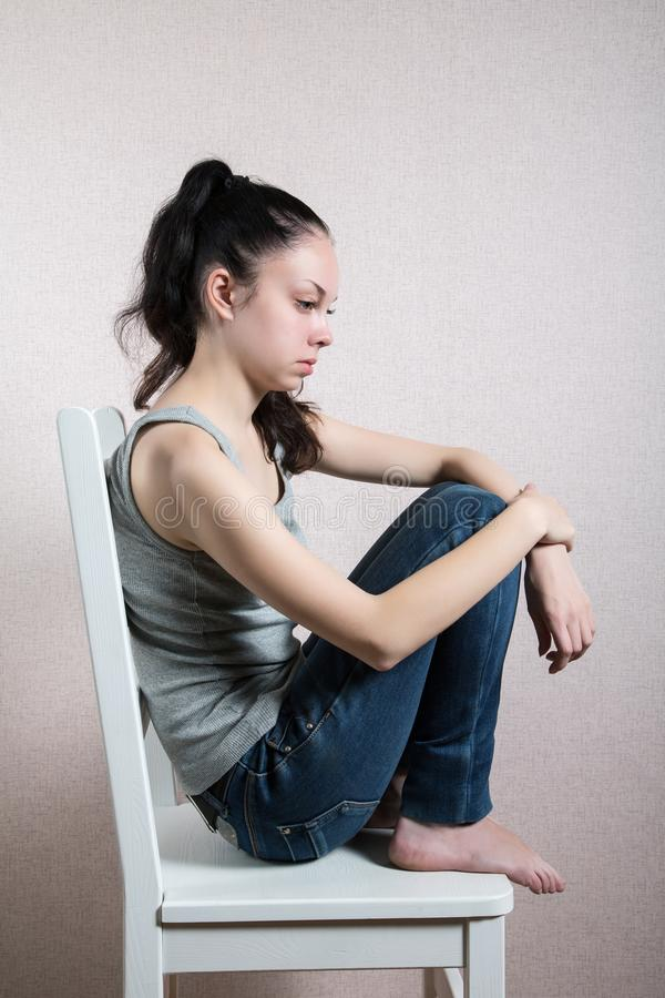 Thoughtful girl sits on a wooden chair royalty free stock photography
