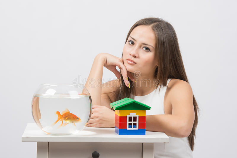Thoughtful girl sitting at a table on which there is an aquarium with goldfish and toy house. A young girl sits next to a round aquarium in which swimming stock photo