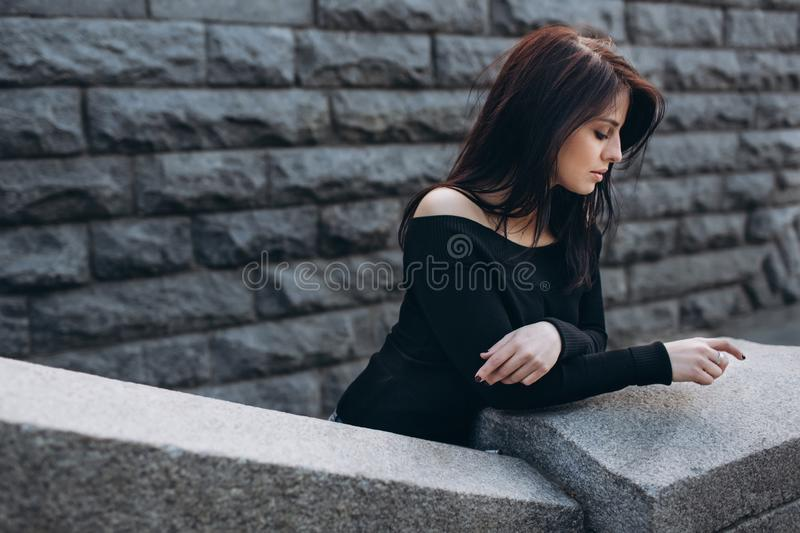 Beautiful girl posing against the backdrop of the urban landscape stock image