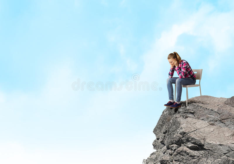 Thoughtful girl. Young thoughtful woman in casual sitting in chair royalty free stock photos