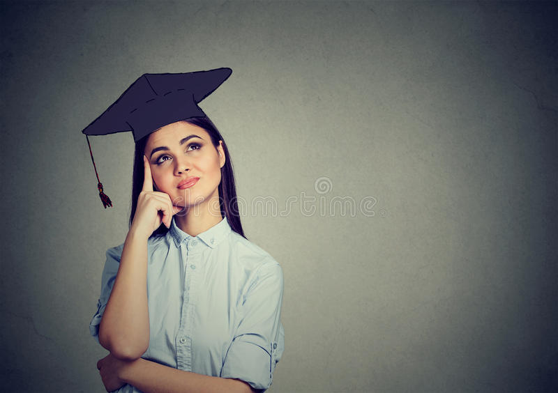 Thoughtful graduate student woman in cap gown looking up thinking. Isolated gray wall background royalty free stock image