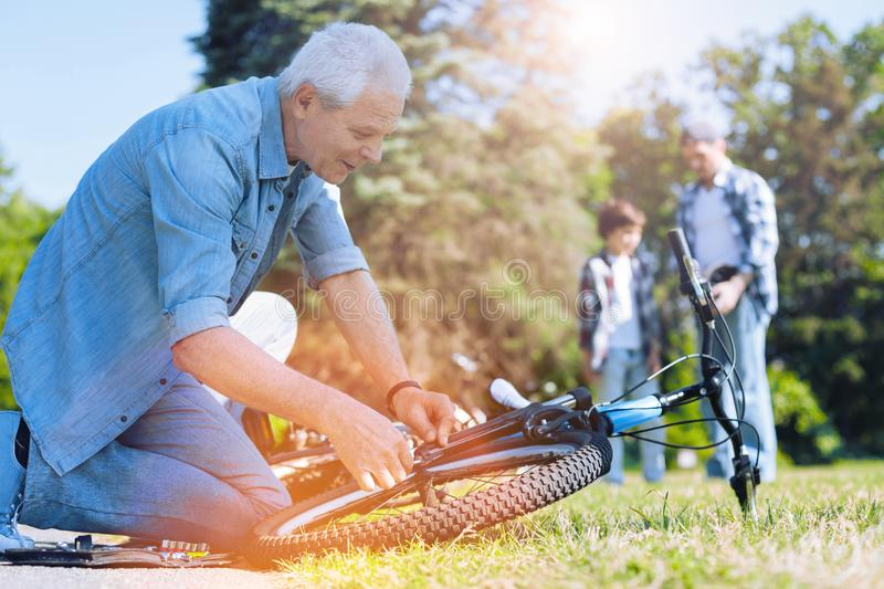 Thoughtful grandfather fixing bike of his little grandchild stock photos