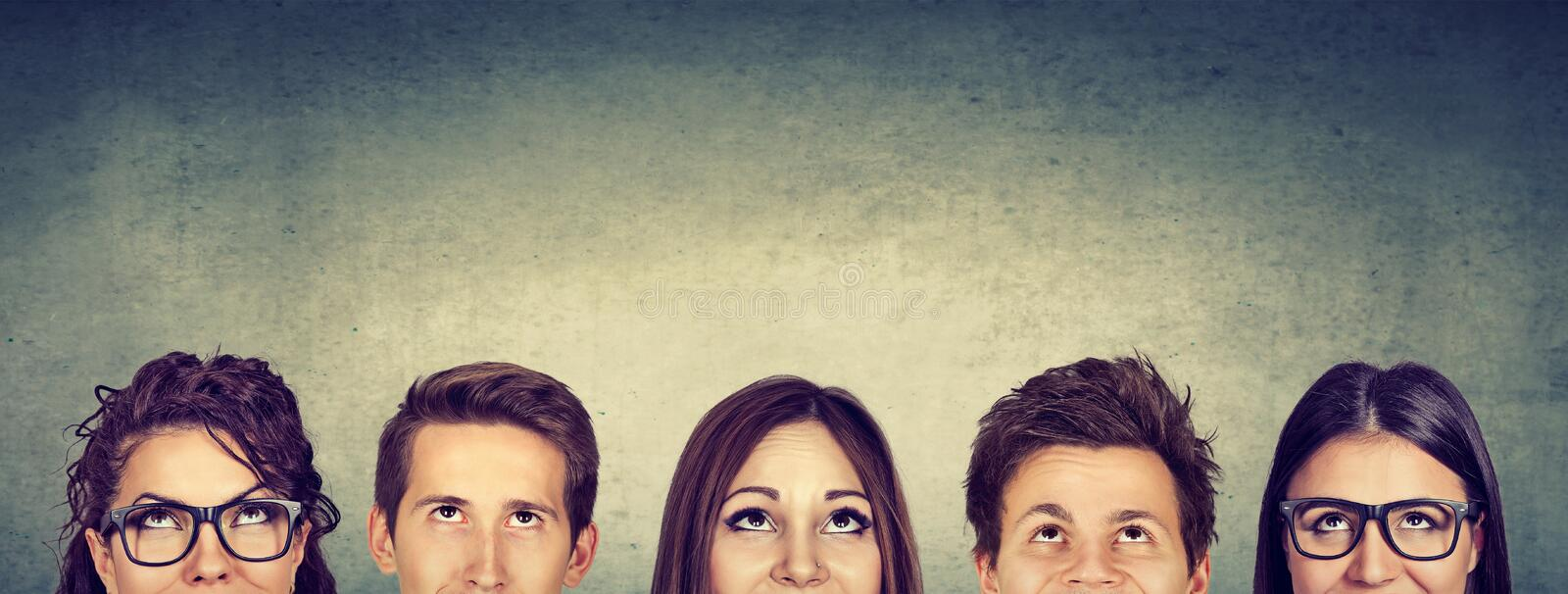 Thoughtful group of people looking up stock photo