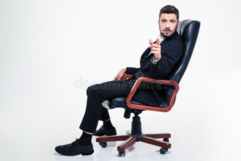Thoughtful handsome business man in office chair pointing on you royalty free stock photos