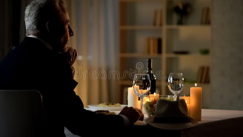 Thoughtful handsome gentleman waiting for woman, sitting at served table, date stock photos