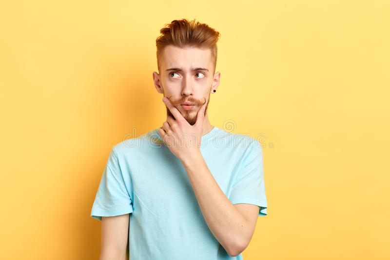 Thoughtful handsome guy keeps his palm on his chin aand looking away royalty free stock photo