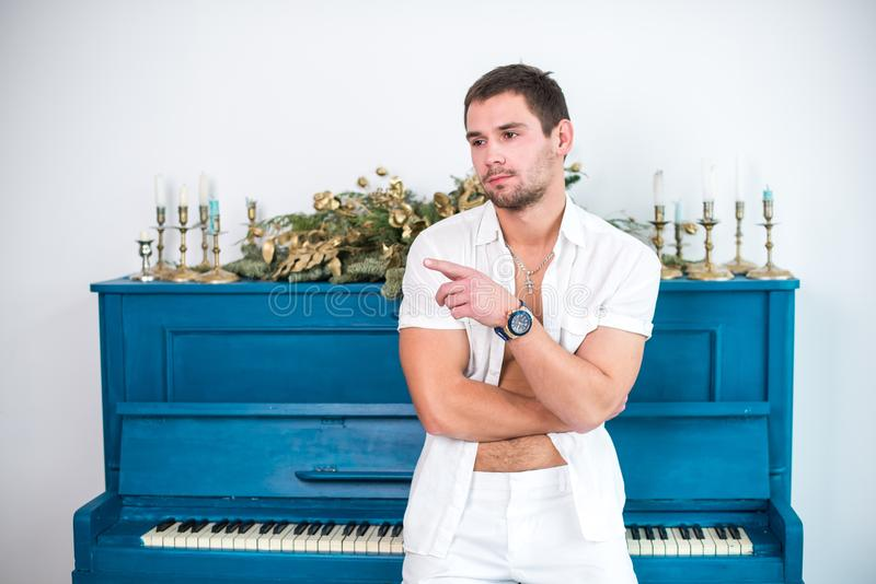 Thoughtful, handsome man with a beard in white clothes against the background of a piano, a rasped shirt with a bare torso royalty free stock photography