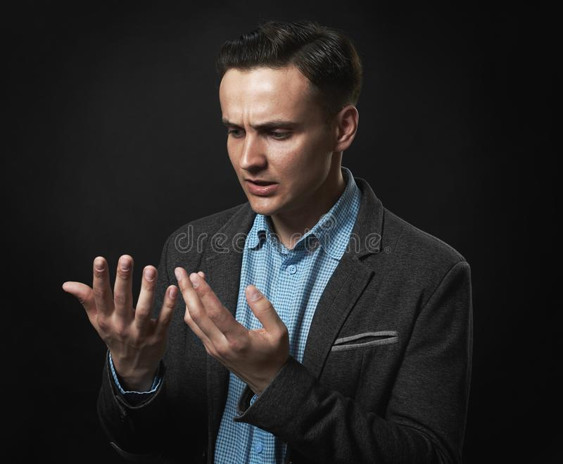 Thoughtful handsome man is looking at his hands stock photography