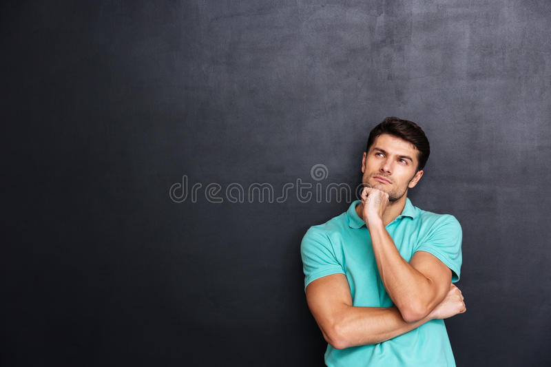 Thoughtful handsome young man standing and thinking royalty free stock photography
