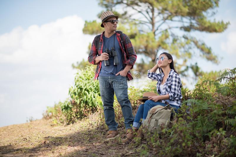 Thoughtful hiking couple looking away while relaxing royalty free stock photography
