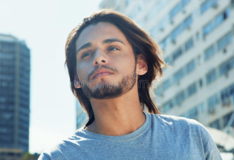Thoughtful hipster with long brunette hair in the city stock photography