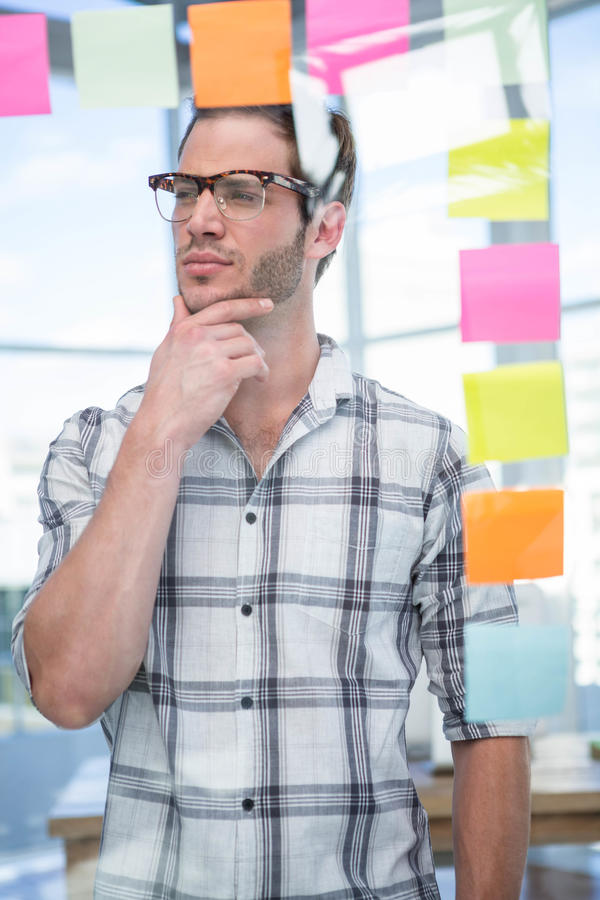 Thoughtful hipster man with post-it royalty free stock photo