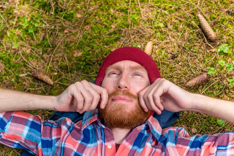 thoughtful hipster stroking his red beard, a portrait of a curtain, a man lying on the ground in the forest royalty free stock photos