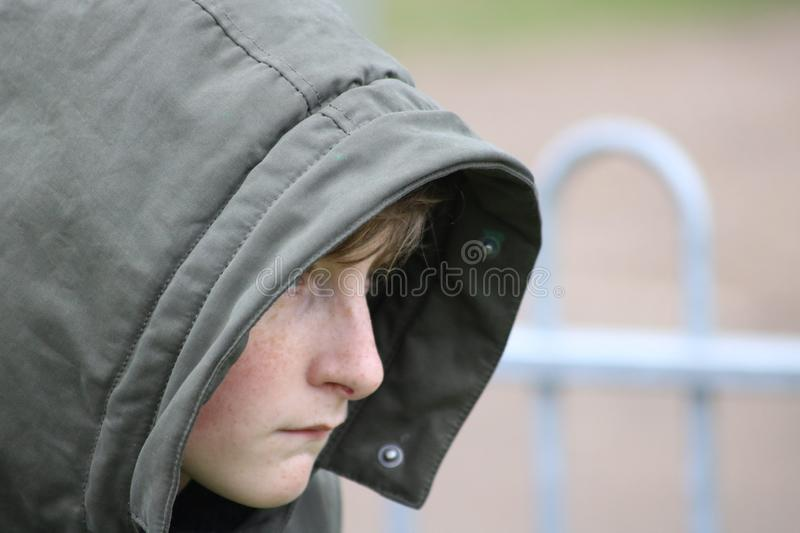 Thoughtful hooded youth on park bench royalty free stock photo