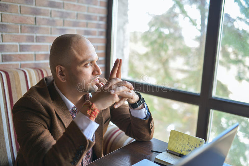 Thoughtful indian business man, sitting near window and looking outside stock image